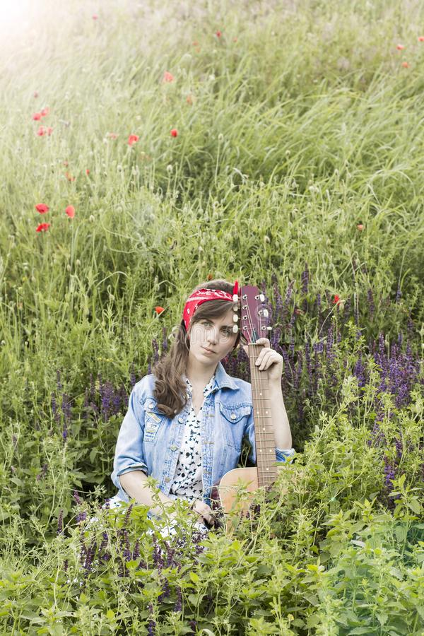 Beautiful girl with a guitar in poppies. Young woman on the grass. A teenager in a denim jacket and a red bandage. Retro stock image