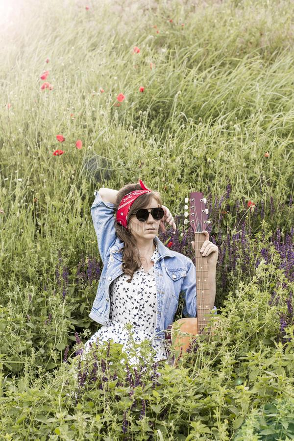 Beautiful girl with a guitar in poppies. Young woman in sunglasses on the grass. A teenager in a denim jacket and a red bandage. stock photography