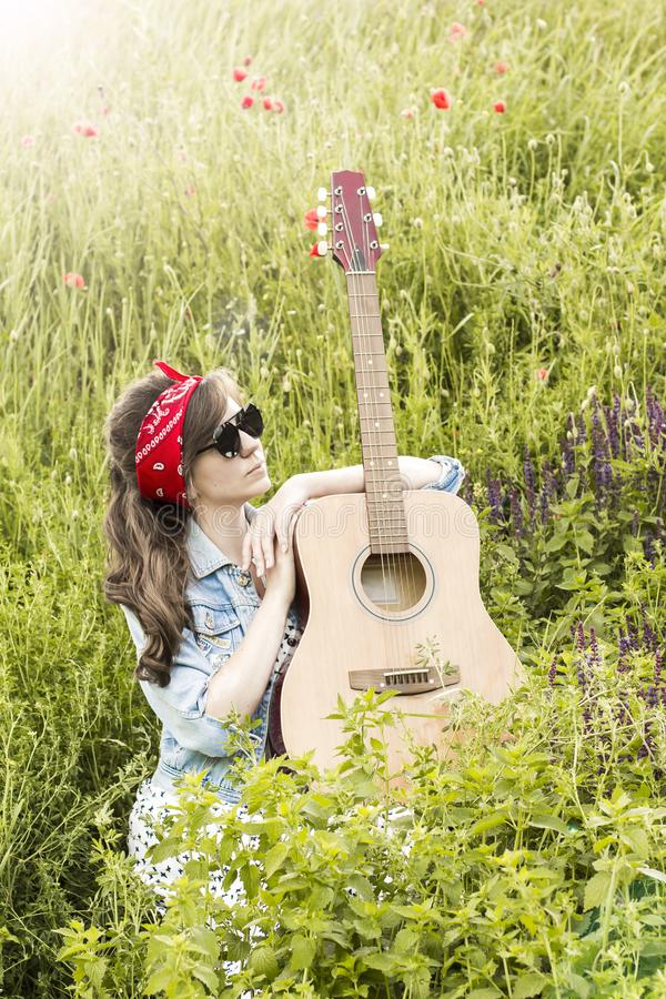 Beautiful girl with a guitar in poppies. Young woman in sunglasses on the grass. A teenager in a denim jacket and a red bandage. R stock photos