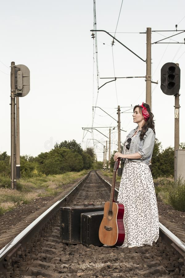 Beautiful girl with a guitar. Pretty woman with old suitcases on the train tracks. A teenager in a denim jacket, a long dress and royalty free stock image