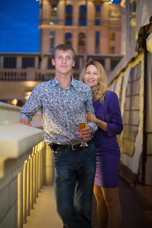 Beautiful girl and a guy with a beer stock photography