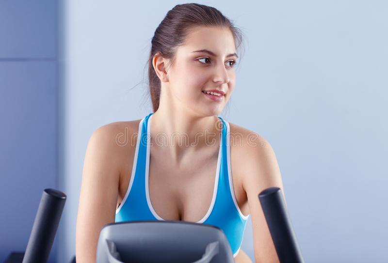 Beautiful girl at the gym exercising on trainers. Beautiful girl royalty free stock photo
