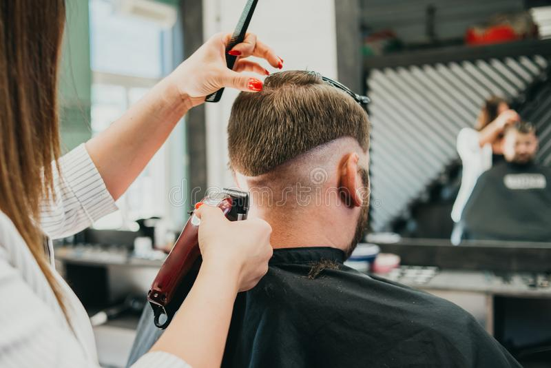 Beautiful girl hairdresser cuts a bearded man in the salon stock image