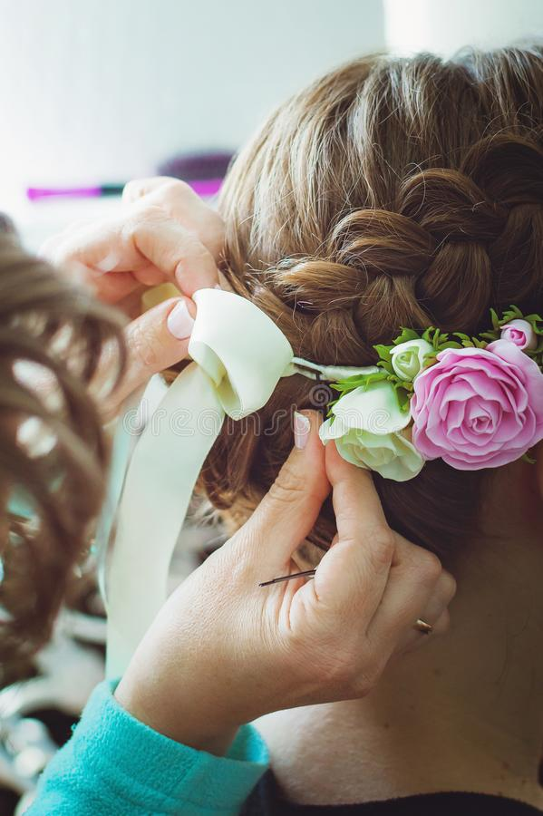 Beautiful girl hairdresser weaves a braid close-up, in a beauty salon. Professional hair care and creating hairstyles, ribbon and stock images