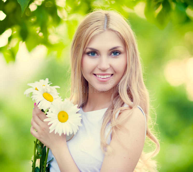 Beautiful girl. Beautiful happy smiling young woman with daisies royalty free stock images