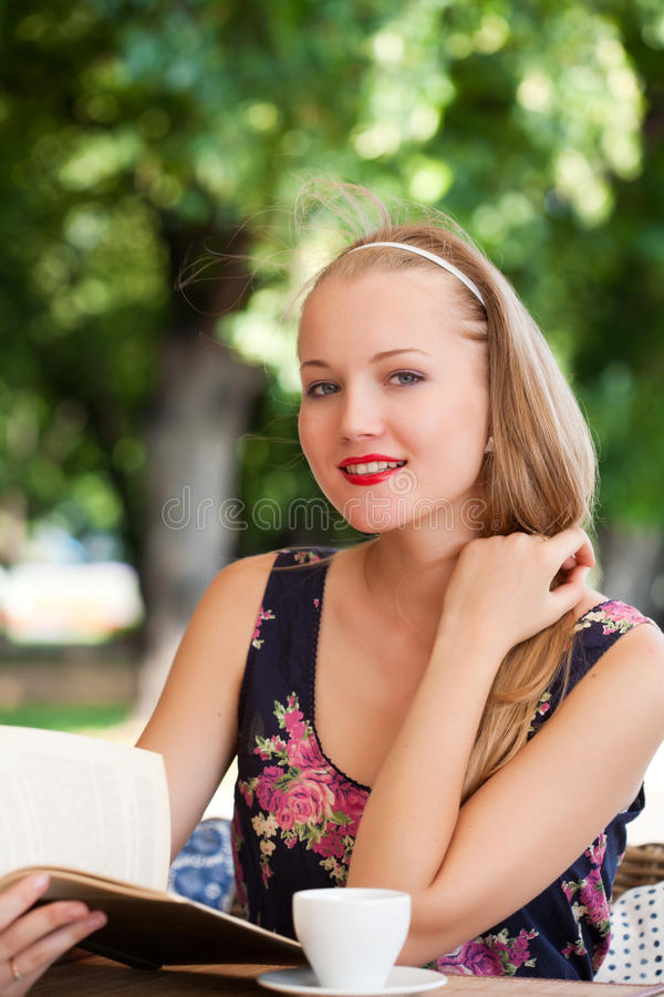 Beautiful girl has a rest in street cafe stock photo
