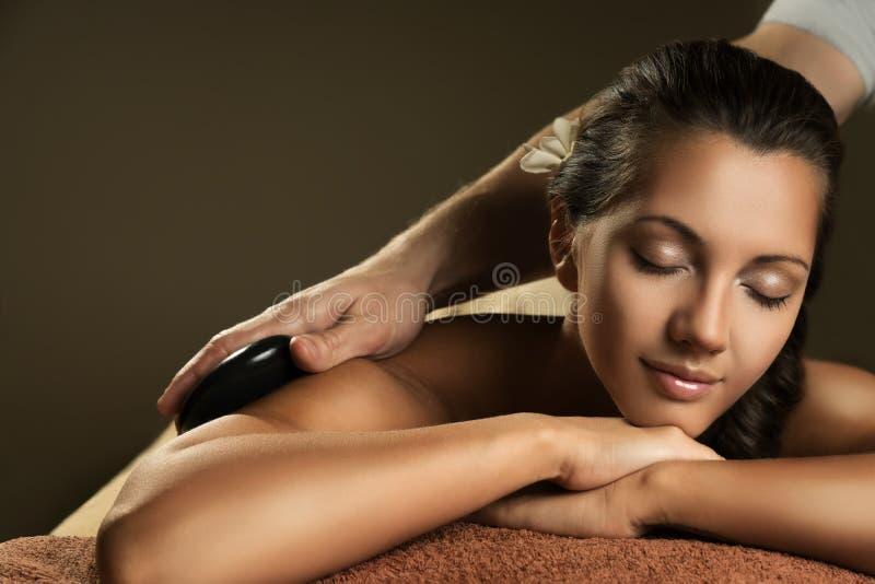 Beautiful girl has stone massage. Beautiful girl has hot stone massage. Spa treatment royalty free stock photos