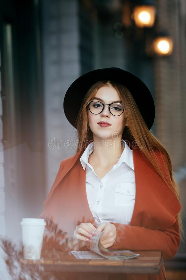 Beautiful girl with Hat and glasses with coffee and a magazine royalty free stock image