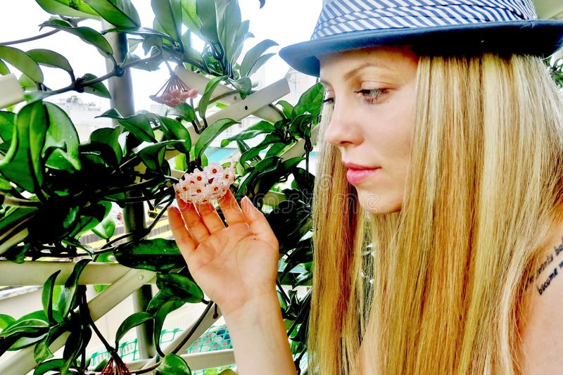 Beautiful girl in a hat looks at a flower stock image