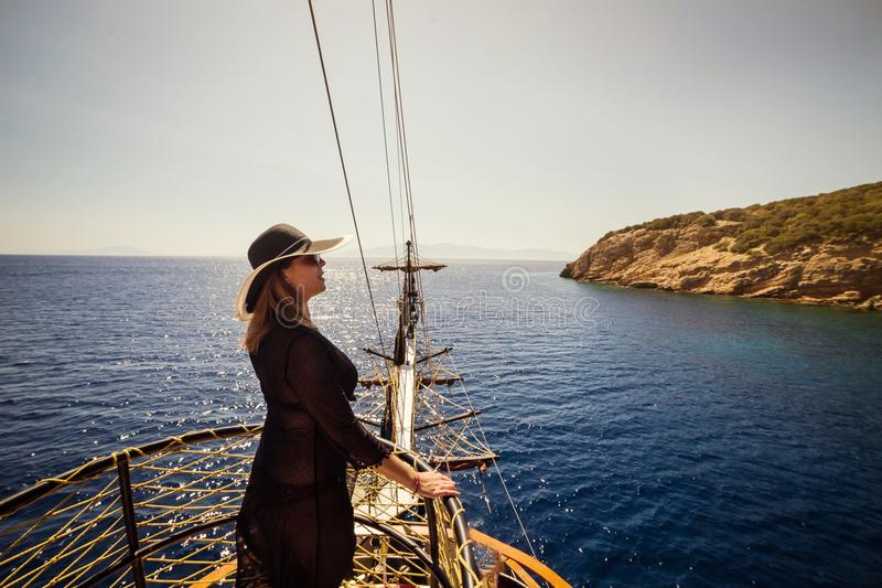 Beautiful girl in hat relaxing on the boat and looking at the is royalty free stock photo