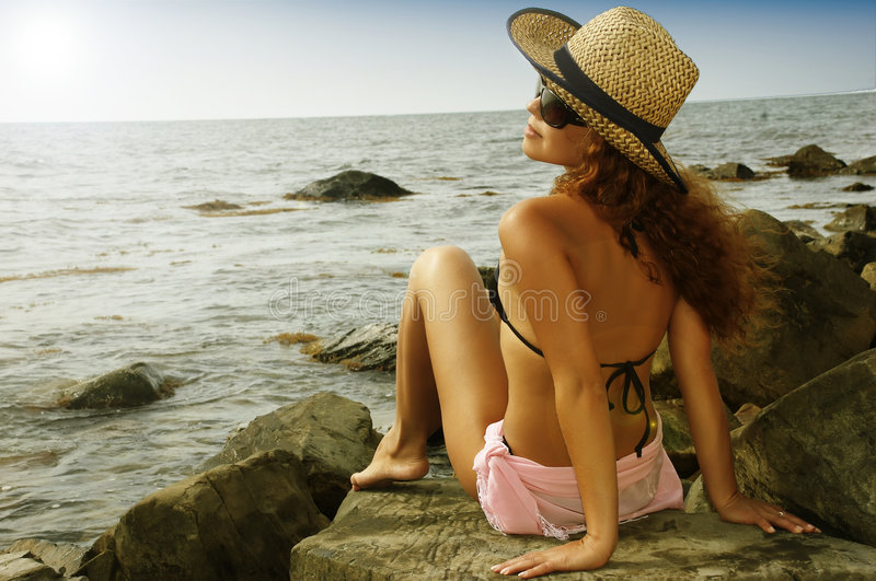 Beautiful girl in a hat of sunburn on a beach. The beautiful woman sits on a beach stock photos