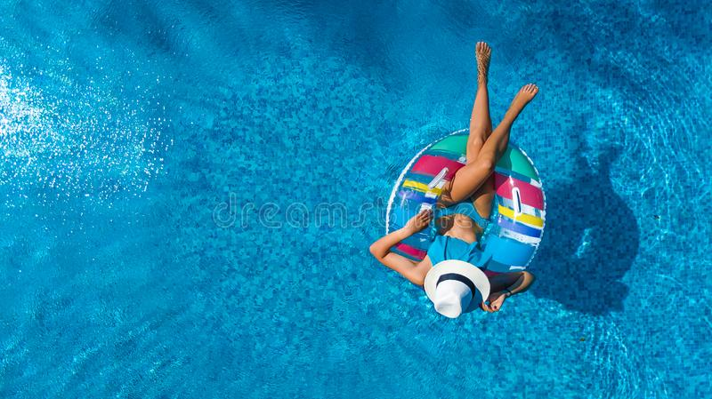 Beautiful girl in hat in swimming pool aerial drone view from above, woman relaxes and swims on inflatable ring donut and has fun stock photo