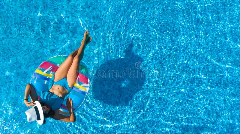 Beautiful girl in hat in swimming pool aerial top view from above, woman relaxes and swims on inflatable ring donut and has fun. In water on family vacation royalty free stock images