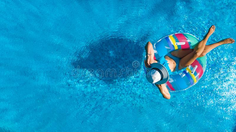 Beautiful girl in hat in swimming pool aerial top view from above, woman relaxes and swims on inflatable ring donut and has fun. In water on family vacation royalty free stock photography