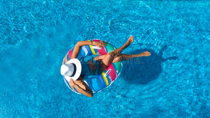 Beautiful girl in hat in swimming pool aerial top view from above, woman relaxes and swims on inflatable ring donut and has fun. In water on family vacation stock photo
