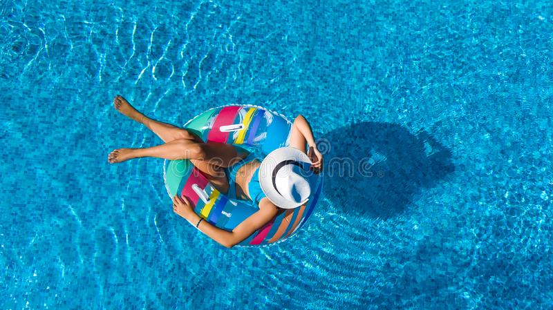 Beautiful girl in hat in swimming pool aerial top view from above, woman relaxes and swims on inflatable ring donut and has fun. In water on family vacation royalty free stock photo