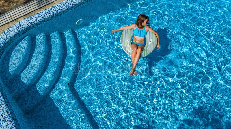 Beautiful girl in hat in swimming pool aerial top view from above, young woman relaxes and swims on inflatable ring donut stock photo