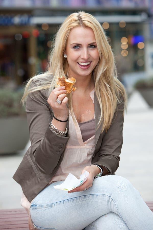 Beautiful girl having a burger stock photography