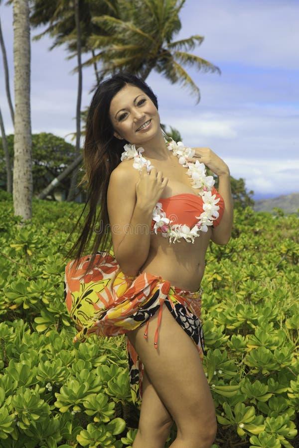 Beautiful girl in a hawaii garden royalty free stock photo