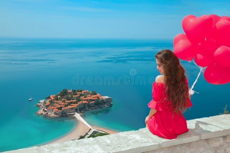 Beautiful girl with heart balloons over Sveti Stefan island in B. Udva, Montenegro. Happy brunette traveler sightseeing Adriatic Sea, Balkans. Summer travel stock images