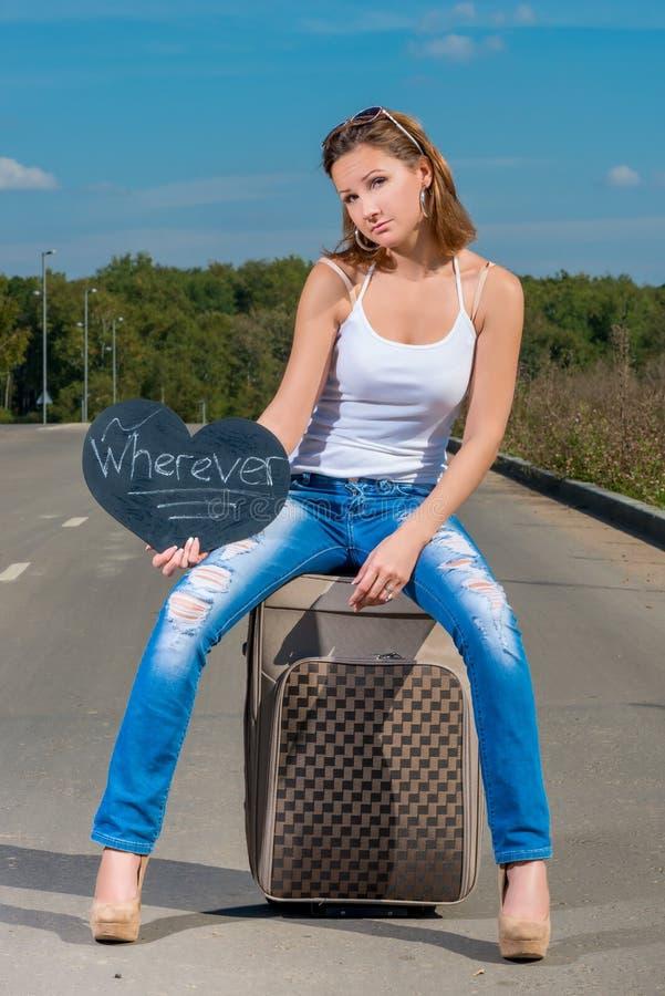 Beautiful girl hitchhiking with luggage. Portrait of a beautiful girl hitchhiking with luggage stock image