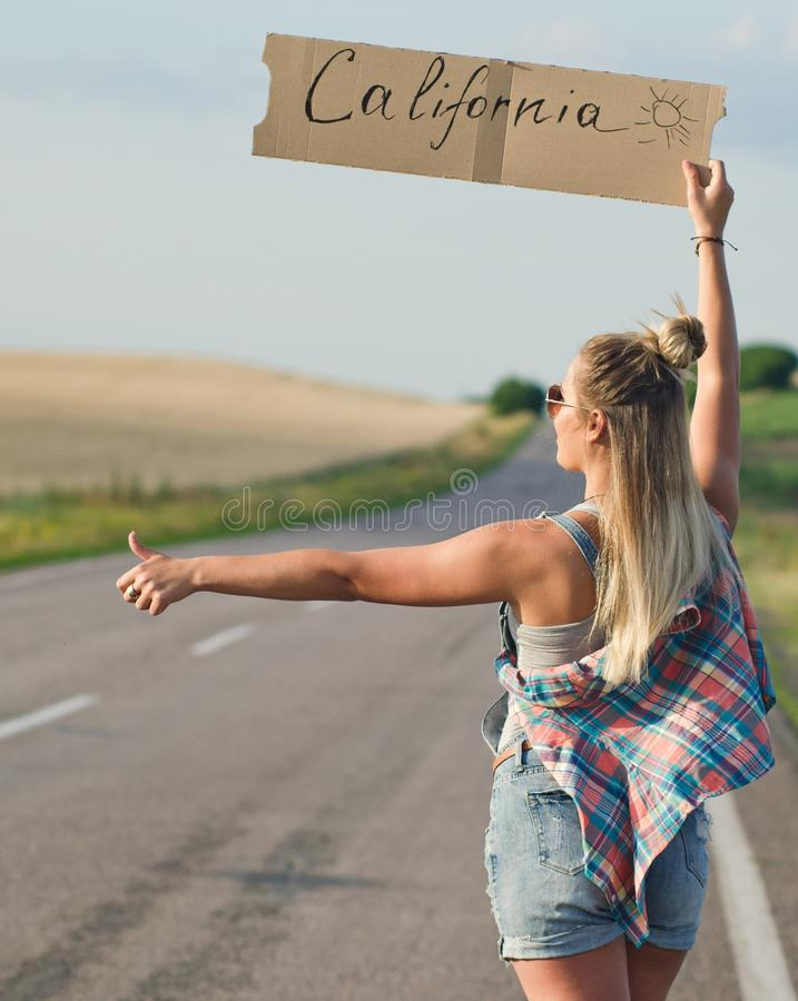 Beautiful girl hitchhiking on the road traveling. Blonde holding sign while hitchhiking on the road in summertime stock photo