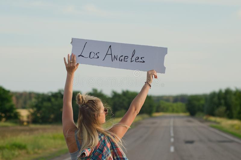 Beautiful girl hitchhiking on the road traveling. Blonde holding sign while hitchhiking on the road in summertime royalty free stock photography
