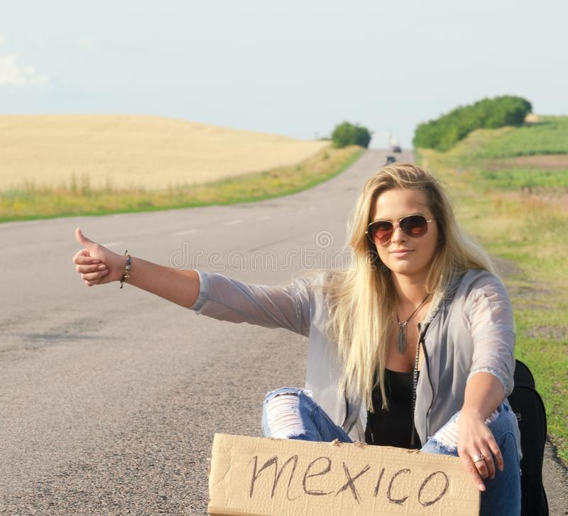 Beautiful Girl Hitchhiking On The Road Traveling. Blonde holding sign while hitchhiking on the road in summertime stock image