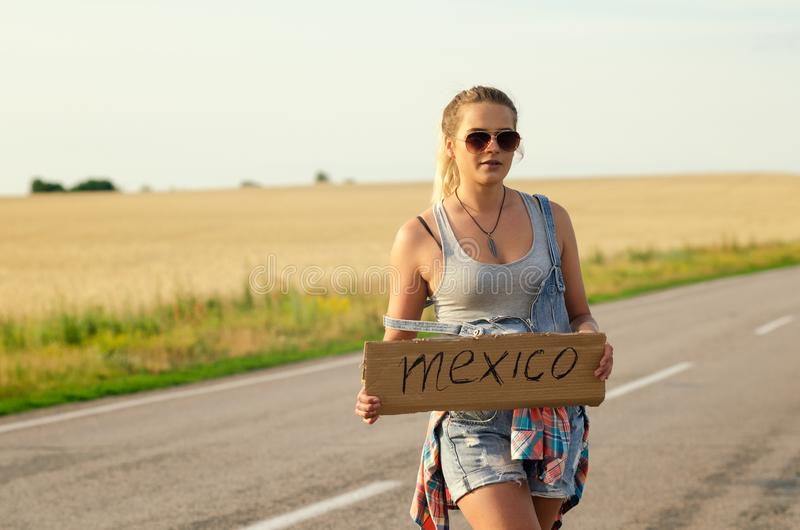Beautiful Girl Hitchhiking On The Road Traveling. Blonde holding sign while hitchhiking on the road in summertime royalty free stock photos