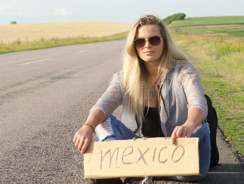 Beautiful Girl Hitchhiking On The Road Traveling. Blonde holding sign while hitchhiking on the road in summertime stock photography