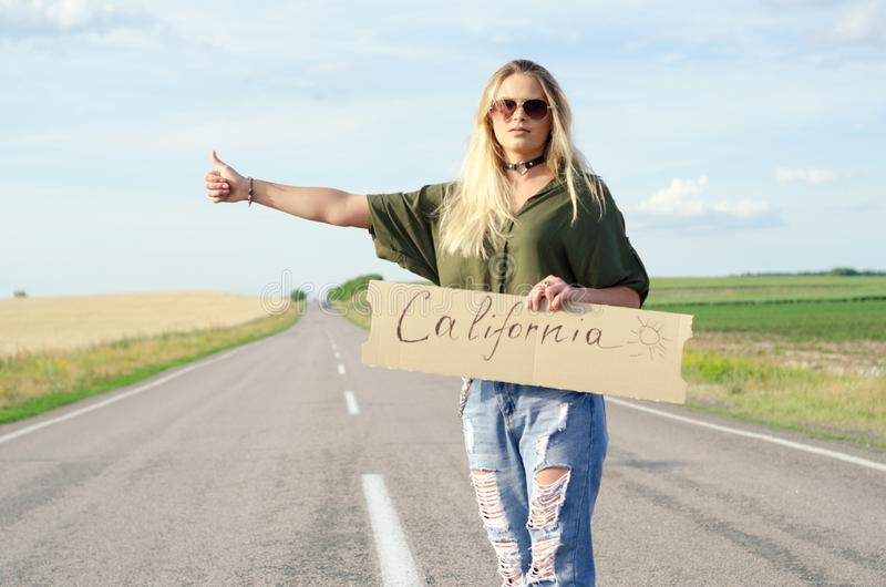Beautiful Girl Hitchhiking On The Road Traveling. Blonde holding sign while hitchhiking on the road in summertime royalty free stock images