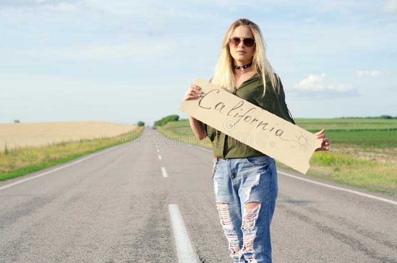 Beautiful Girl Hitchhiking On The Road Traveling. Blonde holding sign while hitchhiking on the road in summertime stock photos