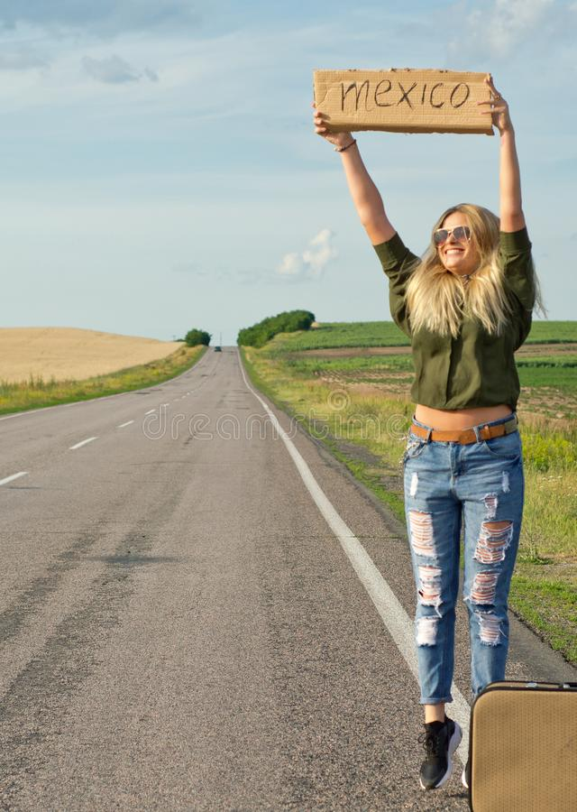 Beautiful girl hitchhiking on the road traveling. Serious blonde holding sign while hitchhiking on the road in summertime stock image