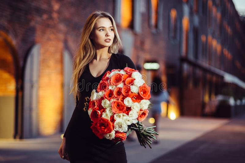 Beautiful girl hold and walk with rose flower bouquet after delivery in the city. Beautiful girl hold and walk with rose flower bouquet after delivery in the stock images