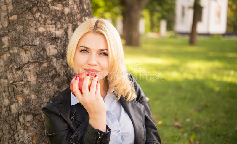 Beautiful girl holding an apple near the tree royalty free stock image