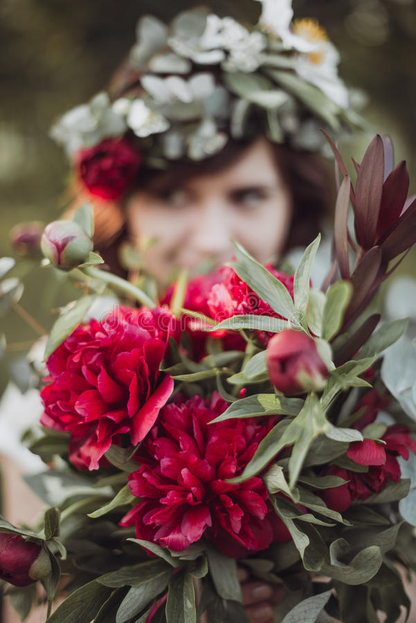 Beautiful girl holding bouquet of peonies royalty free stock image