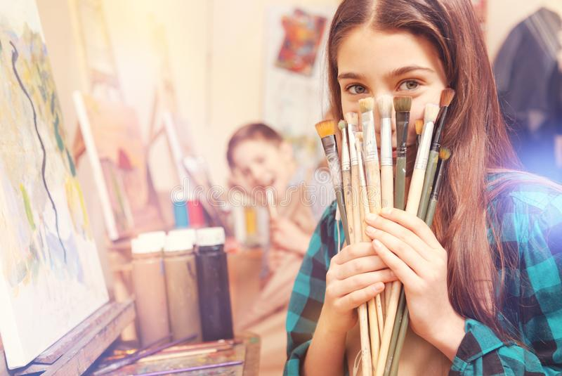 Beautiful girl holding bunch of messy painting brushes royalty free stock photography