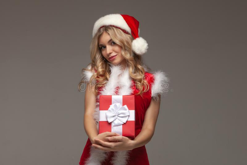 Beautiful girl holding a christmas present. Happy young woman opening a Christmas present box royalty free stock images