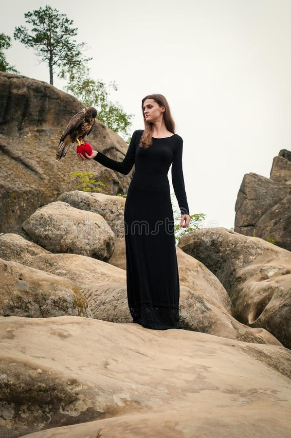 Beautiful girl holding a falcon in her arms. royalty free stock image