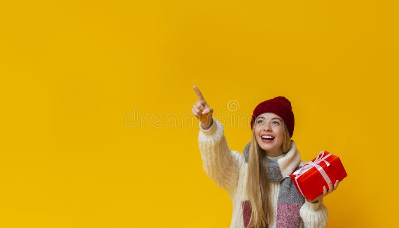 Beautiful girl holding gift and pointing at free space royalty free stock images