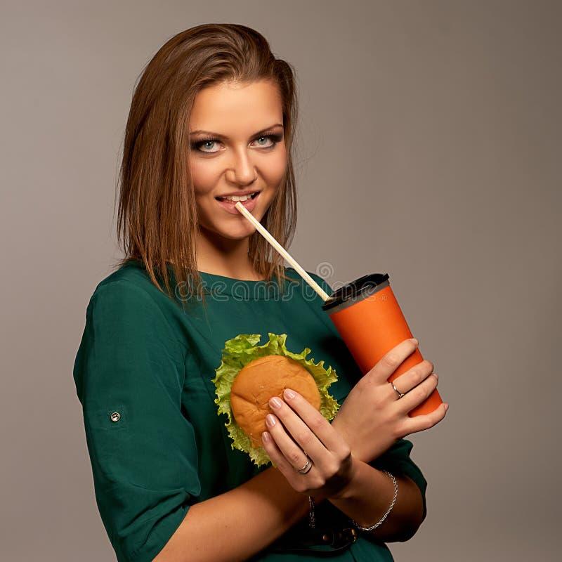 Beautiful girl holding hamburger and cola. Beautiful woman holding hamburger and cola royalty free stock image