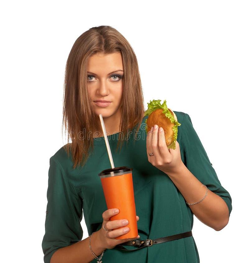Beautiful girl holding hamburger and cola. Beautiful woman holding hamburger and cola isolated on white royalty free stock image