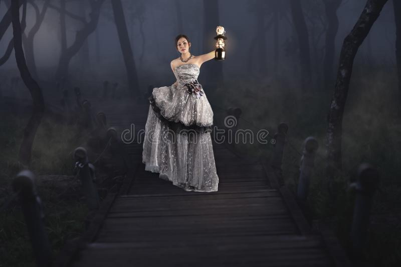 Beautiful girl holding a lantern in the woods royalty free stock images