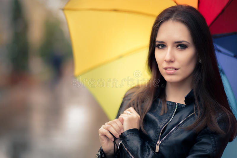 Beautiful Girl Holding a Rainbow Umbrella in Autumn Rain Decor. Fall girl wearing leather jacket outside in rainy weather royalty free stock images