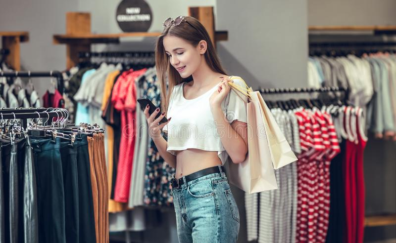 Beautiful girl is holding shopping bags in the mall. stock photo