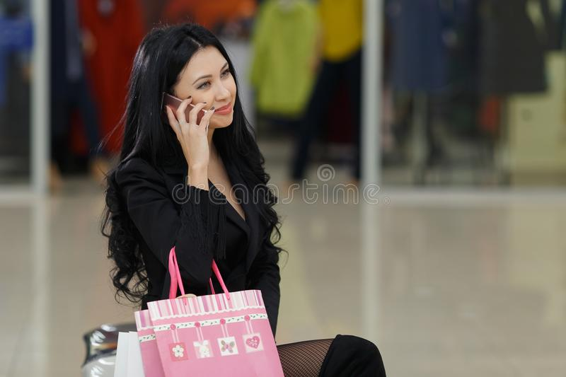 Beautiful girl is holding shopping bags talking on mobile phone in the mall. stock images