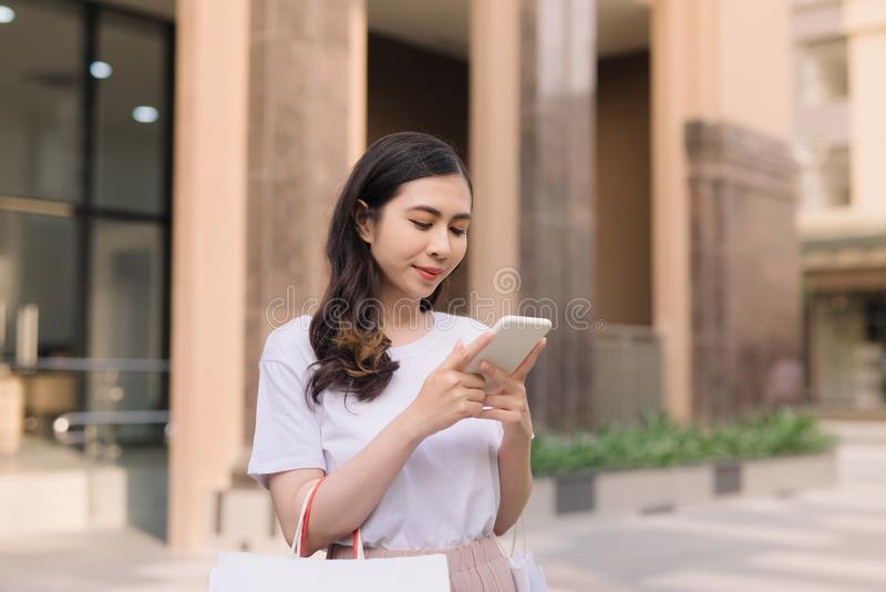 Beautiful girl is holding shopping bags, using a smart phone stock image