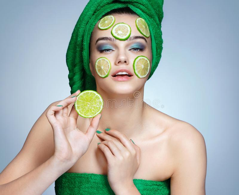 Beautiful girl holding a slice of lime and smiling. royalty free stock photography