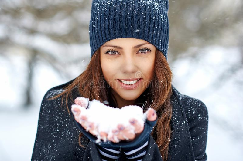 Beautiful girl holding snow in her hands. Winter woman portrait - close up royalty free stock image