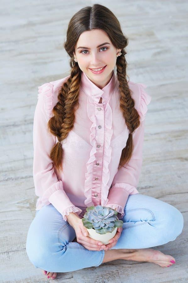 Beautiful girl holding succulent flower pot stock photography
